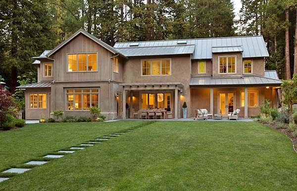 Beautiful Modern Farmhouse With A Backdrop Of Evergreen Trees